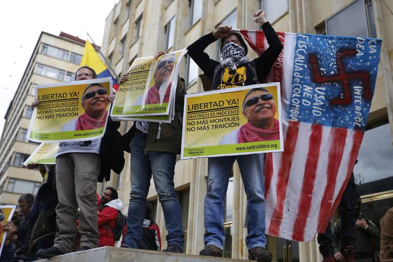 """Três manifestantes carregam cartazes de Santrich, com uma foto do ex-guerrilheiro sob fundo amarelo e a inscrição, em letras pretas, em espanhol: """"Liberdade Já! Santrich é inocente. Não mais montagens. Não mais traição."""". O único cuja cabeça aparece está à direita e segura também uma bandeira dos EUA com uma cruz suástica e menções a CIA, Interpol, USAID, DEA e a Promotoria da Colômbia. Este manifestante usa um lenço preto e branco quadriculado para cobrir o rosto. Todos estão em um palanque ao lado de um prédio."""