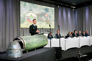 Dutch police officer Paulissen is pictured next to a damaged missile as he presents interim results in the ongoing investigation of the 2014 MH17 crash, during a news conference by members of the Joint Investigation Team in Bunnik