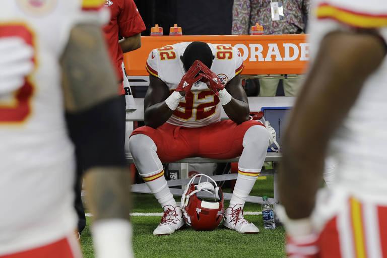O jogador do Kansas City Chiefs, Tanoh Kpassagnon, permanece sentado durante a execução do hino americano, antes de uma partida da última temporada da NFL, em protesto pela violência da polícia contra os negros dos Estados Unidos