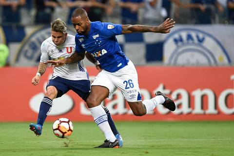 Dede (R) of Brazil's Cruzeiro, vies for the ball with Yeferson Soteldo (L) of Chile's Universidad de Chile, during their 2018 Copa Libertadores match held at Mineirao stadium, in Belo Horizonte, Brazil, on April 26, 2018. / AFP PHOTO / DOUGLAS MAGNO