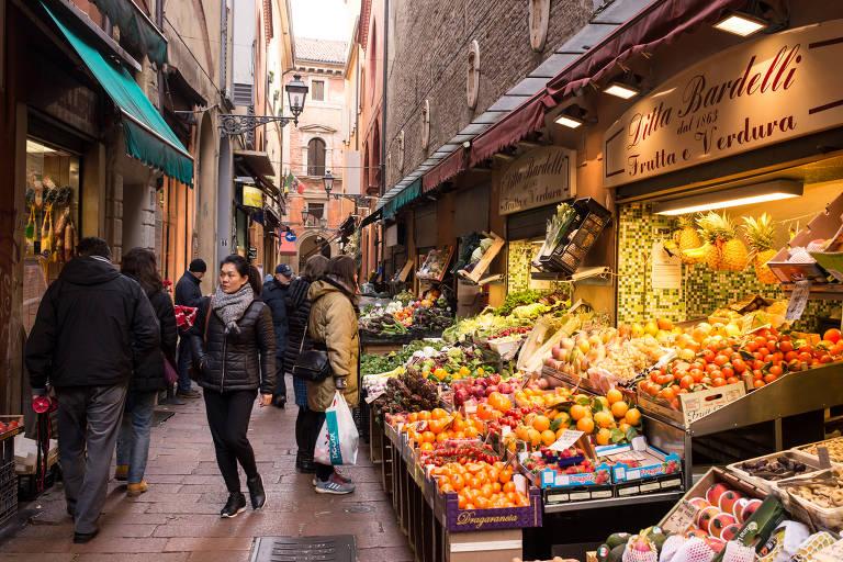 Viela estreita no centro de Bolonha. De um lado, há vitrines de lojas e do outro, ocupando parte da rua, bancas com diversas frutas e legumes, à frente das mercearias
