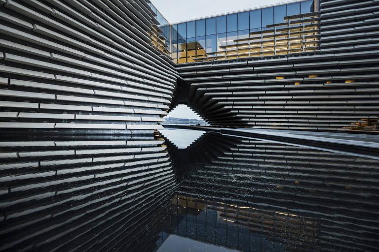 Detalhe do prédio do museu V&A em Dundee, na Escócia. A construção fica acima de um espelho d'água e tem aparência moderna, com acabamento em telhas brancas dispostas em fileiras e vidro na parte superior
