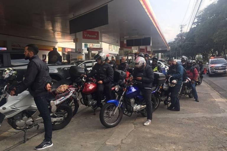 fila de motoqueiros em posto de gasolina
