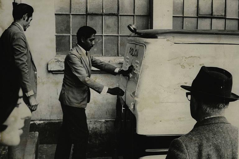 """""""Funcionários do IML tentam ocultar o transporte de um cadáver; alegaram que não era o de João da Cunha, embora todos que rodeavam o carro fúnebre soubessem de que se tratava do boiadeiro"""", diz a legenda da imagem do acervo da Folha"""