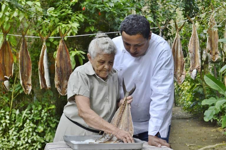 O chef Eudes Assis e sua mãe, Madalena, secam peixes no varal, ao sol, no litoral norte de São Paulo