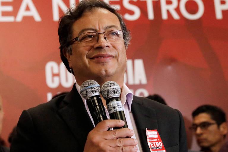 De blazer preto e camisa rosa claro, Petro sorri enquanto segura dois microfones; na lapela, um adesivo de campanha. O fundo é vermelho, com letras brancas.