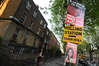 A sign for a polling station is surrounded with Pro-Choice and Pro-Life posters ahead of a 25th May referendum on abortion law, in Dublin