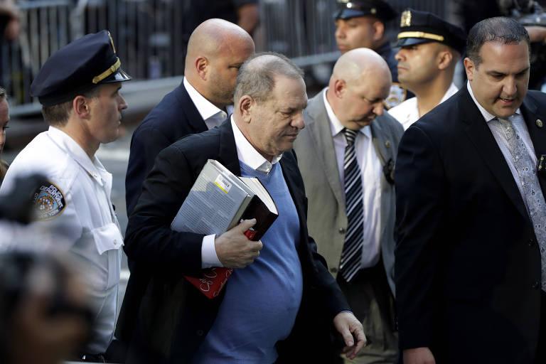 Harvey Weinstein chega à delegacia em Nova York ao lado de policiais, segurando livros e com a cabeça baixa