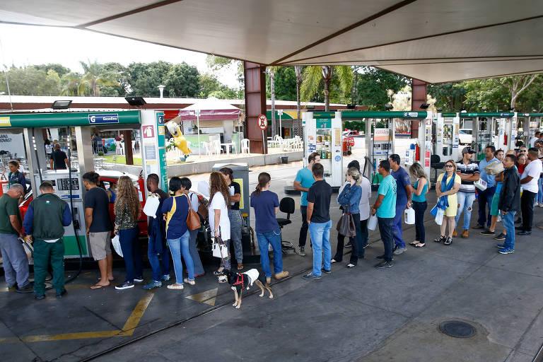 fila de pessoas pra encherem galões de gasolina em posto