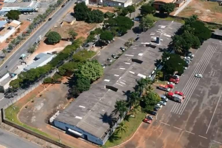 Imagem aérea mostra galpão por cima, cercado de viaturas dos bombeiros