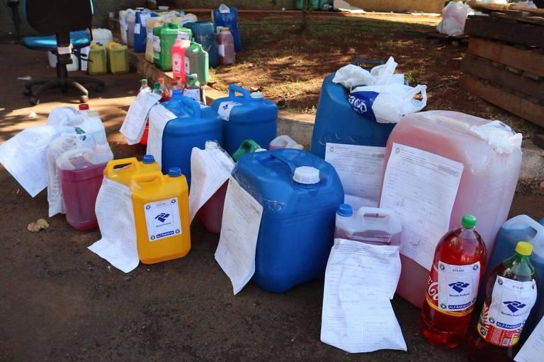combustível dentro de galões e garrafas pet com papel com o logo da receita federal colado sobre eles