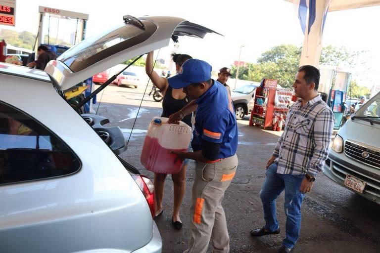 frentistas abastecem carros e recebem de motoristas