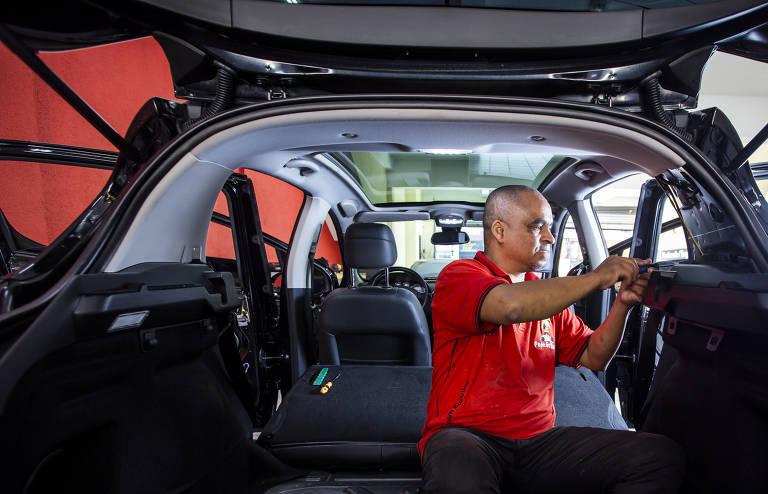 3) Funcionário desmonta porta-malas do carro para procurar origem de barulho