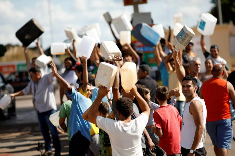 Pessoas carregam galões vazios de gasolina em frente a posto em Brasília