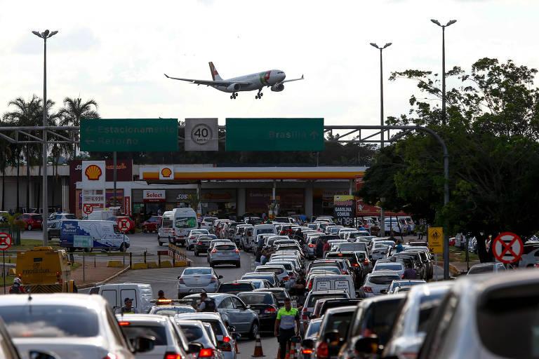 Avião se aproxima para pousar no aeroporto de Brasilia, enquanto uma fila de carros tenta abastecer no posto de gasolina próximo à pista de pouso