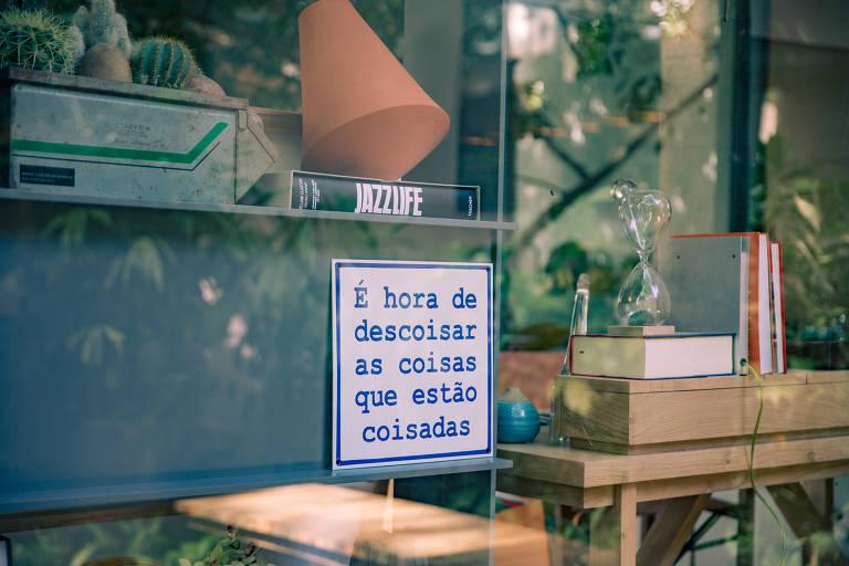 """Ambiente decorado com a placa """"É hora de descoisar as coisas que estão coisadas"""""""