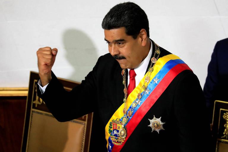 De terno preto, gravata vermelha e camisa branca, Maduro usa a faixa e o colar presidencial e ergue o punho esquerdo em uma das tribunas da Constituinte