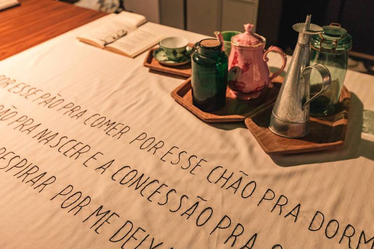 """Toalha bordada com trecho da música """"Deus lhe Pague"""", de Chico Buarque: """"Por esse pão pra comer, por esse chão pra dormir"""""""