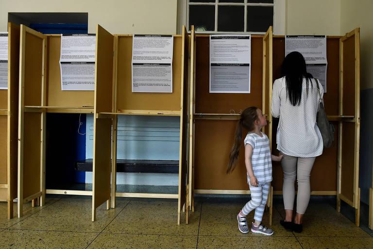 De camisa branca, calça legging cinza e sapato preto, mulher de cabelo preto aparece de costas em uma das cabinas de votação no canto direito da imagem. A filha aparece do lado esquerdo, de conjunto listrado azul claro e branco. Ao lado esquerdo, outras três cabines de votação feitas de madeira e cortiça, todas com demonstrativos de como votar.
