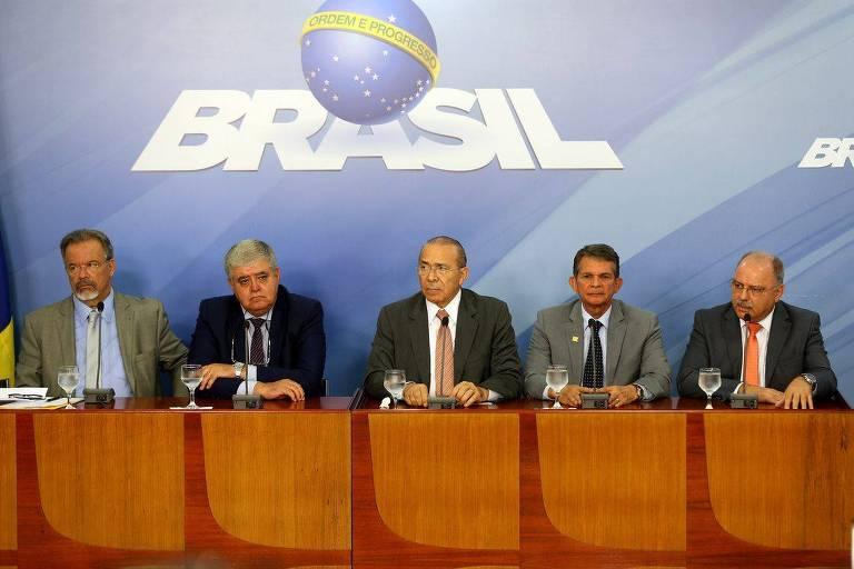 Cinco ministros sentados com o logo do governo estampado na parede ao fundo