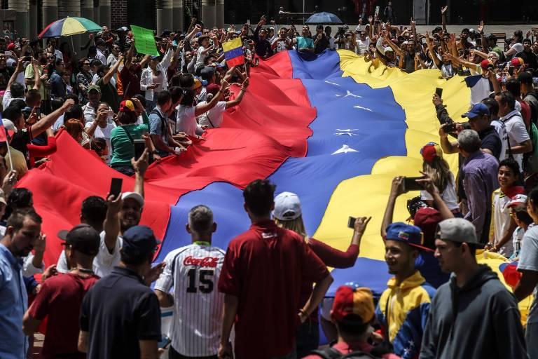 Grupo de dezenas de pessoas agita bandeirão da Venezuela