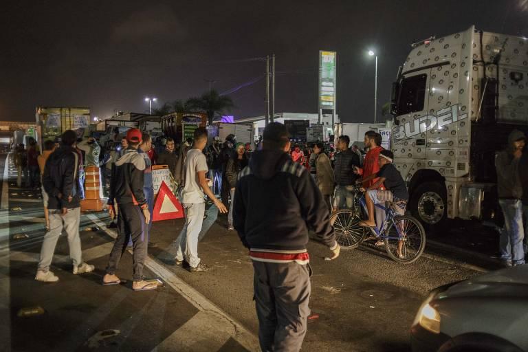 motoristas andam pela pista da  rodovia. Caminhões bloqueiam a via