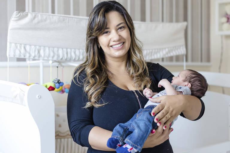 A advogada  Fernanda Prevedello, 37, segura o filho Enrico no colo