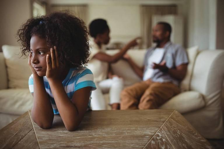 Menina triste e pais brigando ao fundo