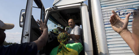 Striking truckers try to stop a fellow driver who hasn't joined the work stoppage to protest rising fuel costs along the highway BR-040, in Duque de Caxias, Brazil, Friday, May 25, 2018. Thousands of Brazilian truckers angry over fuel price hikes blocked roads on Friday, the fifth day of a strike that led thousands of schools to shutter, long lines to form at gas stations and several flights to be canceled. (AP Photo/Silvia Izquierdo) ORG XMIT: XSI102
