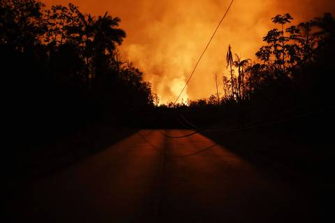 PAHOA, HI - MAY 25: Lava from a Kilauea volcano fissure blocks a roadway and illuminates the night sky in Leilani Estates, on Hawaii's Big Island, on May 25, 2018 in Pahoa, Hawaii. Following a magnitude 4.4 earthquake today centered in the summit region of the Kilauea volcano, an ash plume was sent from the volcano at least 10,000 feet skyward, according to the National Weather Service.   Mario Tama/Getty Images/AFP == FOR NEWSPAPERS, INTERNET, TELCOS & TELEVISION USE ONLY ==
