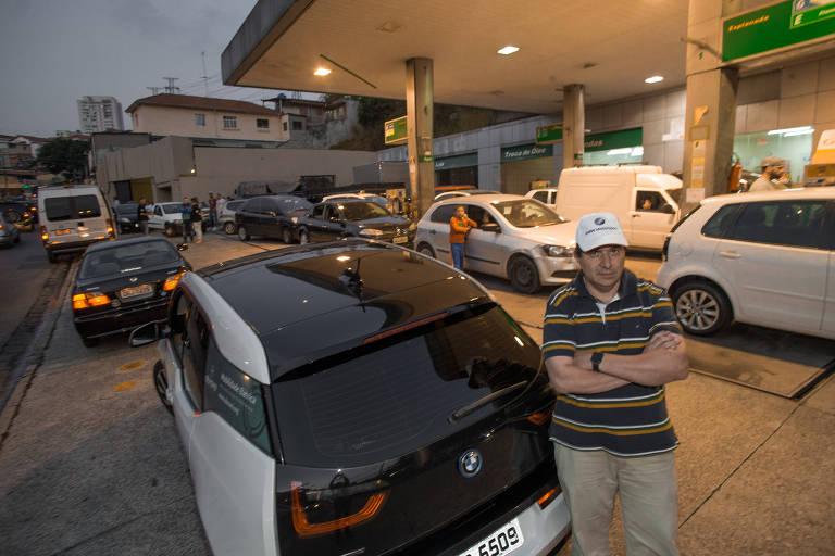 O gestor hospitalar Edgar Escobar posa em posto de gasolina lotado com seu BMW i3 elétrico