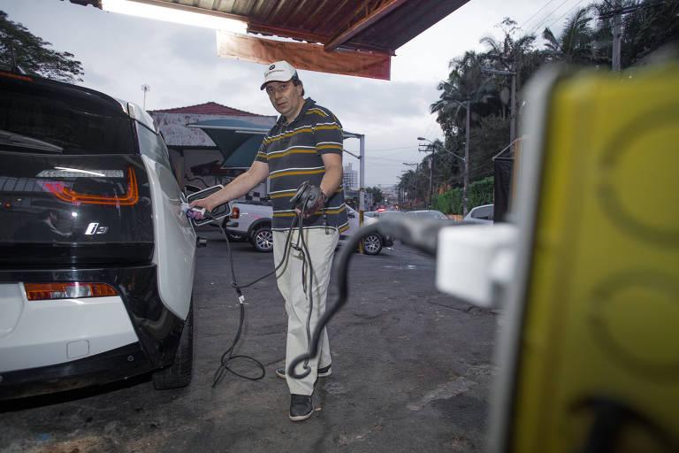 O gestor hospitalar Edgar Escobar abastece seu BMW i3 elétrico em tomada
