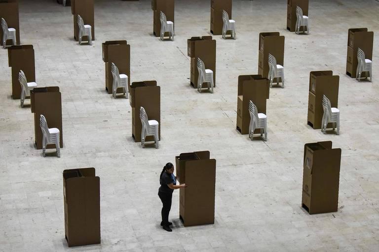 Mulher instala urna de votação em Cali, no oeste da Colômbia