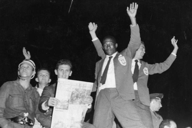 Jogador Djalma Santos acena ao desfilar em carro com a equipe da seleção brasileira após vitória da Copa de 1958