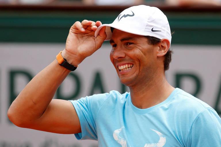 O espanhol Rafael Nadal sorri e coloca a mão no boné em dia de exibição em Roland Garros