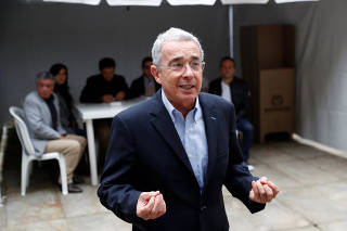 Colombia's former president Alvaro Uribe Velez speaks to the news media after casting his vote in Bogota