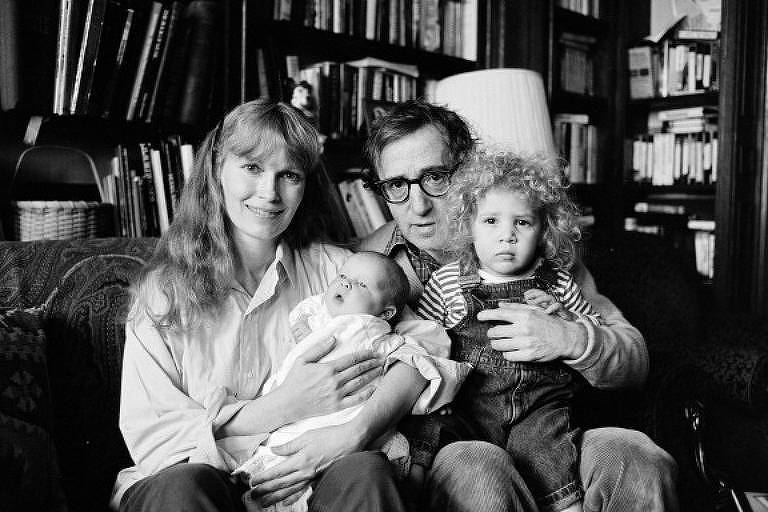 Mia Farrow com o filho Ronan no colo, e Woody Allen segurando a filha Dylan