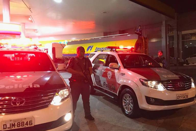 PM segura arma na mão, ao lado de duas viatura. Ao fundo, o caminhão com logo Ipiranga
