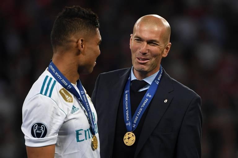 Homem com terno e medalha conversa com homem de camiseta branca e medalha