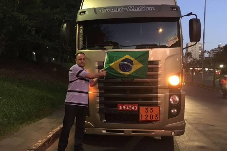 Homem em frente ao caminhão, aponta para bandeira do brasil, colada na frente do veiculo