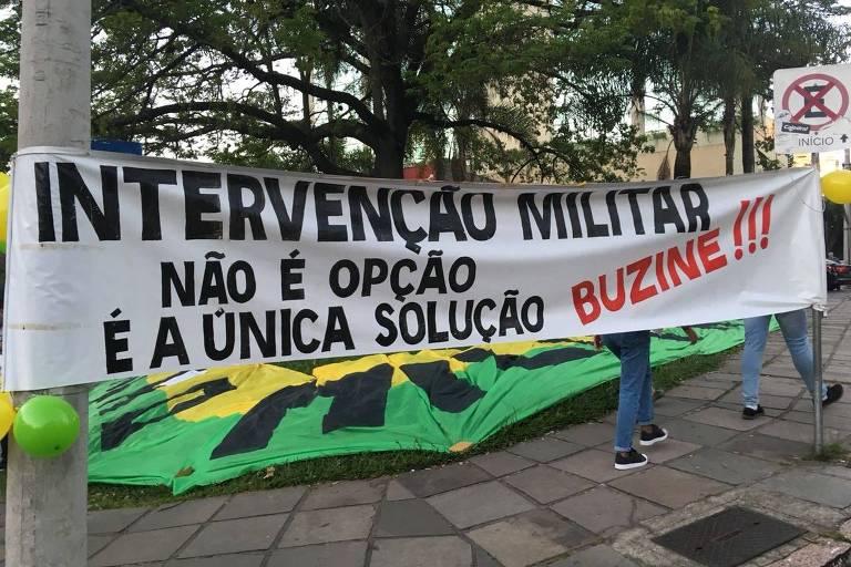 """Faixa com escrito: """"intervenção militar. não é opção é a única solução. Buzine"""""""