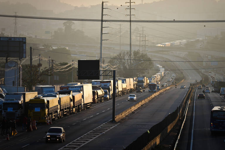Caminhões estacionados bloqueiam faixas de rodovia