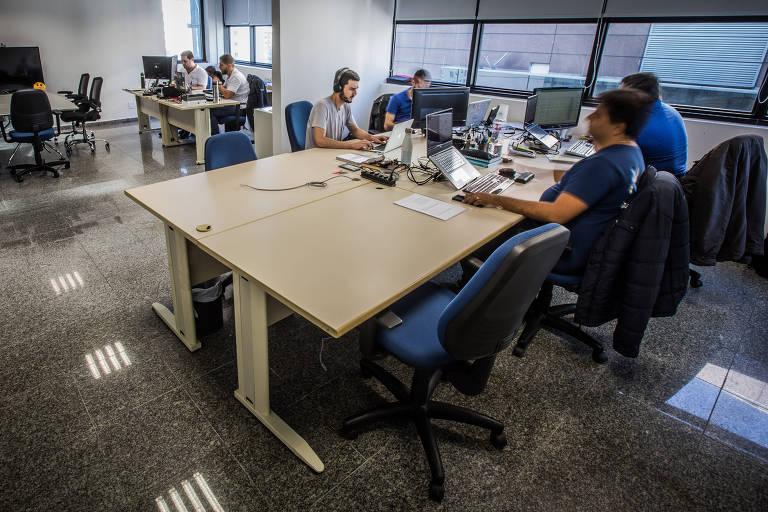 Homens trabalham em uma sala