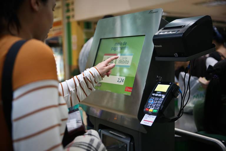 Mulher aperta tecla em tela digital para fazer pagamento