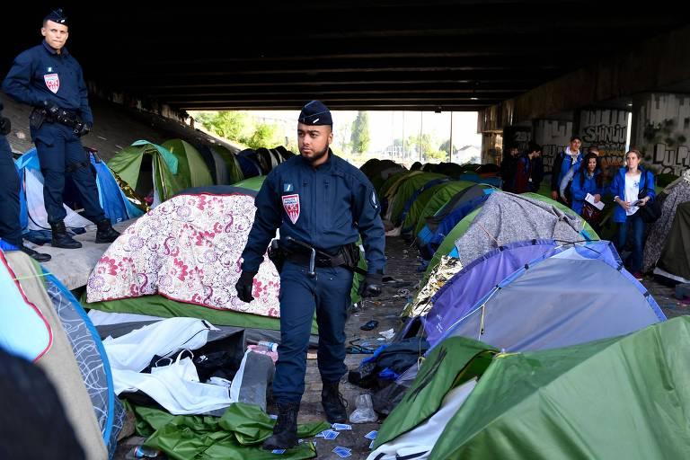 Policiais inspecionam barracas após retirada de imigrantes de campo de refugiados no canal de Saint-Denis em Paris