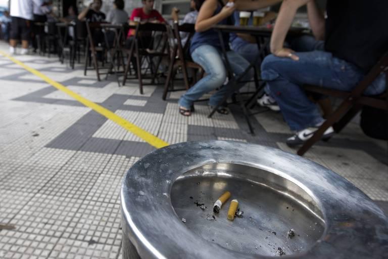 Cinzeiros na calçada da Vila Madalena, em São Paulo (SP). Ao fundo, pessoas sentadas em um bar