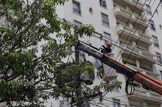FILE PHOTO: A technician of Electropaulo works on an electrical post along a street during a 30-hour power outage at the Pinheiros neighbourhood in Sao Paulo