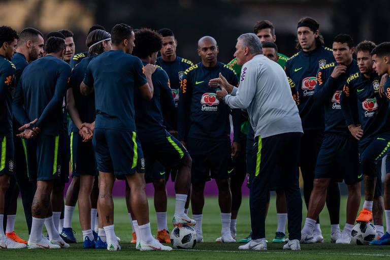 Um grupo de jogadores da seleção brasileira conversam com o técnico Tite
