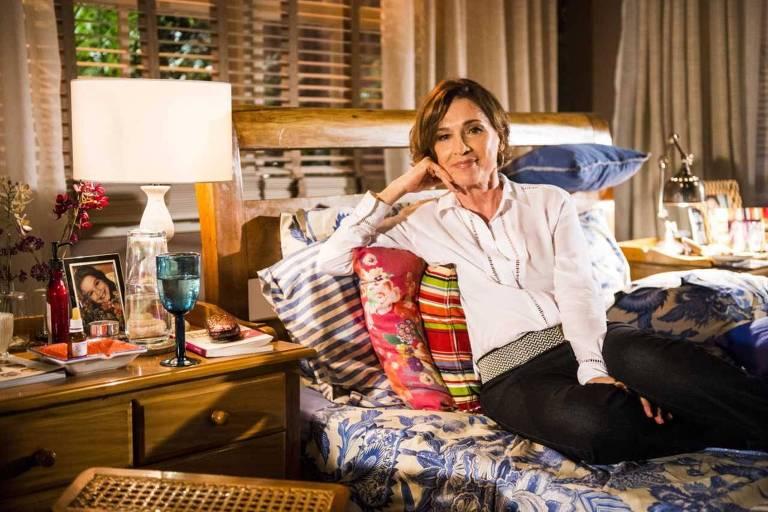 A atriz Natália do Vale deitada em uma cama com a mão no rosto