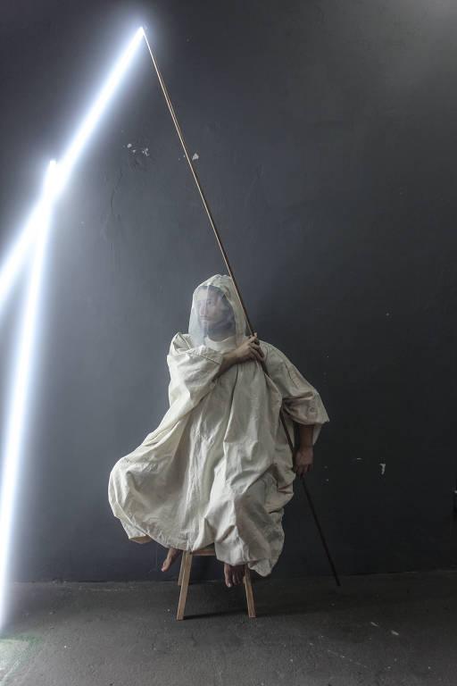 Homem sentado com uma roupa branca segura um cabo com uma lanterna de onde sai luz